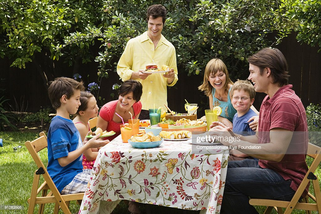 Smiling group of adults and kids eating outdoors : Stock Photo