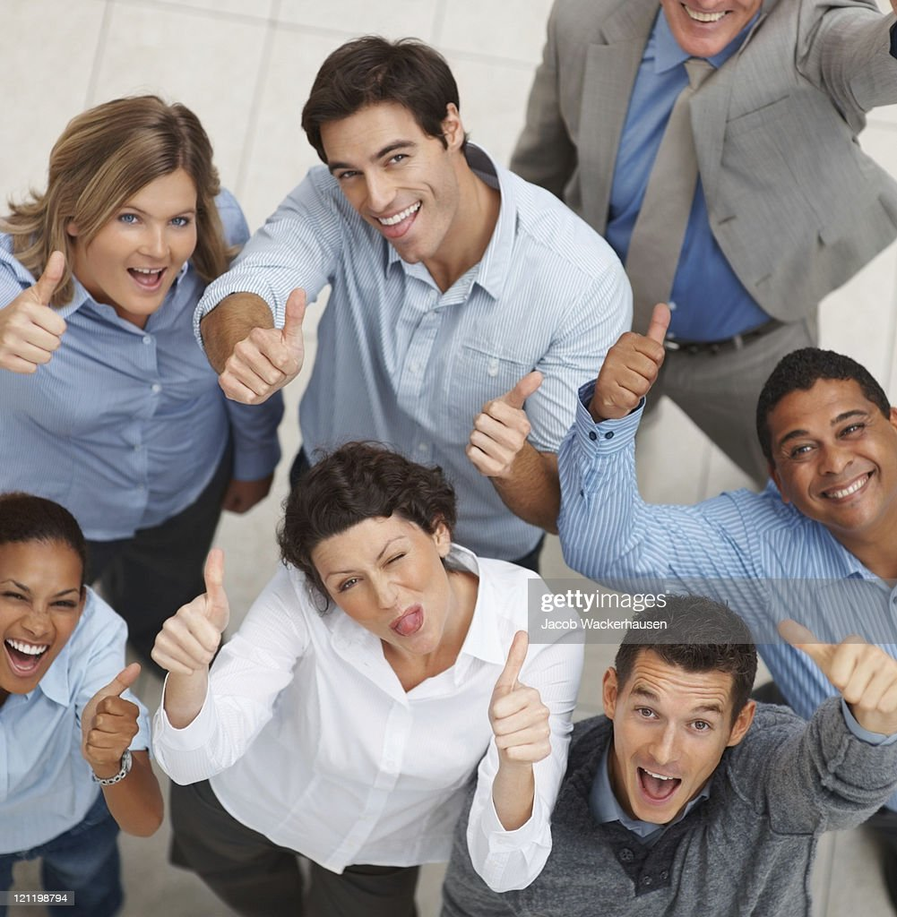 Smiling group of business people showing you a success sign : Stock Photo