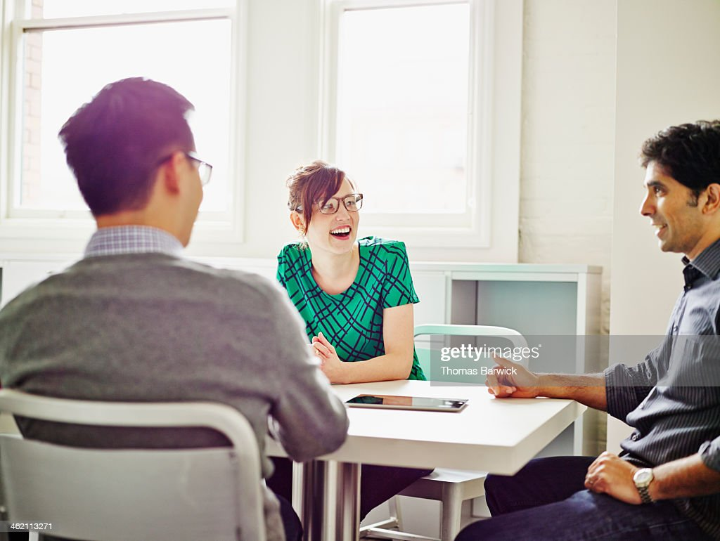 Smiling group of coworkers discussing project : Stock Photo