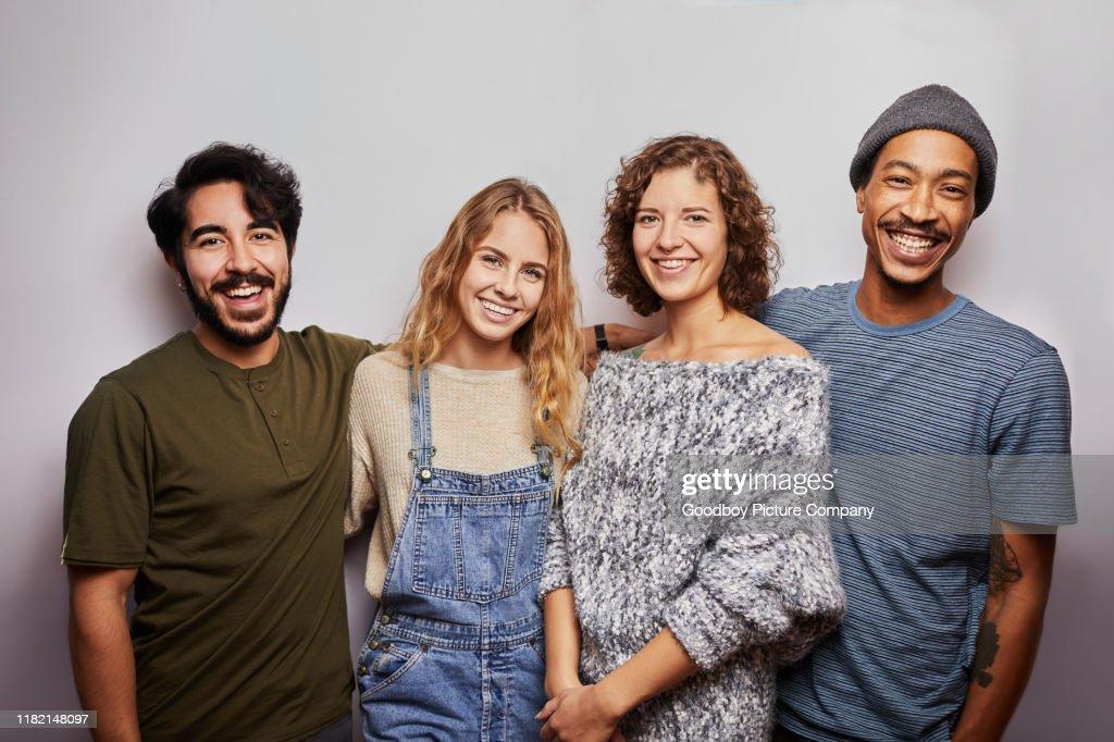 Lächelnde Gruppe von verschiedenen jungen Freunden vor grauem Hintergrund : Stock-Foto