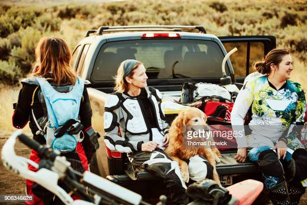 Smiling group of female friends relaxing after riding dirt bikes in desert on summer evening