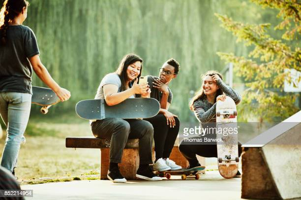 Smiling group of female skateboarders looking at smartphone in skate park