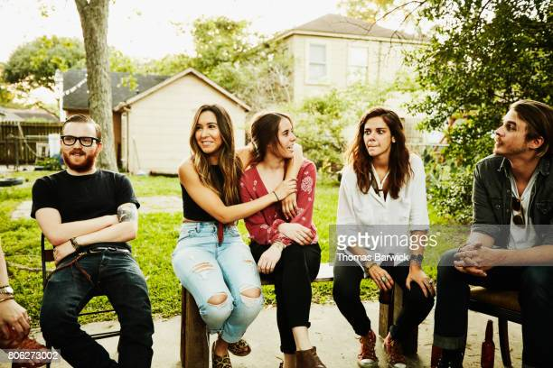 smiling group of friends in discussion in backyard on summer evening - adults only stock pictures, royalty-free photos & images
