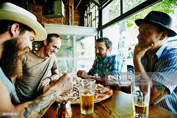 Smiling group of friends sharing pizza and beers