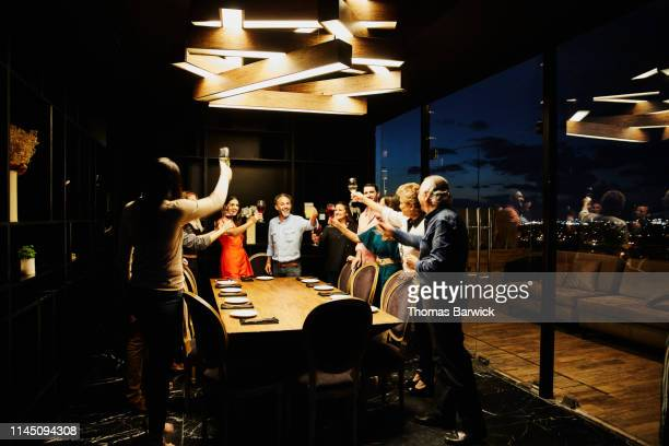 Smiling group of friends toasting before dining in private dining room in restaurant