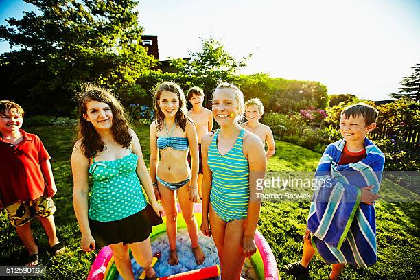 Smiling group of kids in swimsuits in backyard
