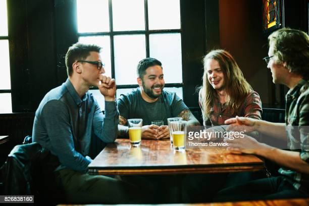 Smiling group of male friends hanging out at table in bar