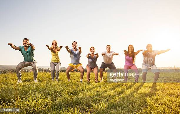 Smiling group of people doing squats and exercising in nature.