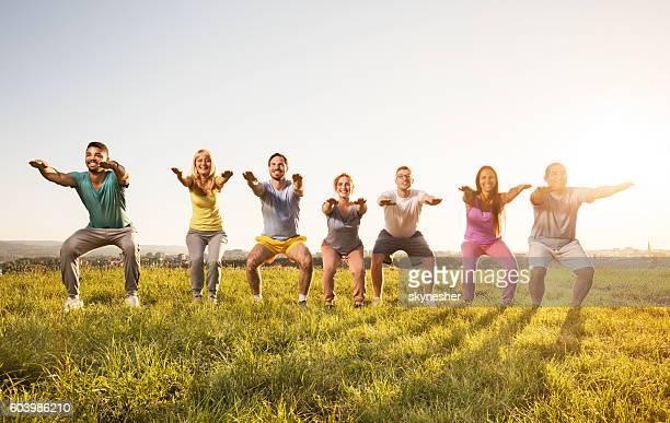 smiling group of people doing squats and exercising in nature. - aufwärmen stock-fotos und bilder