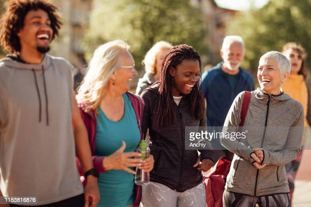 smiling group of people walking together outdoors - community stock pictures, royalty-free photos & images