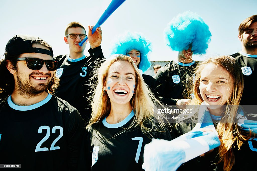 Smiling group of soccer fans cheering in stadium : Stock Photo