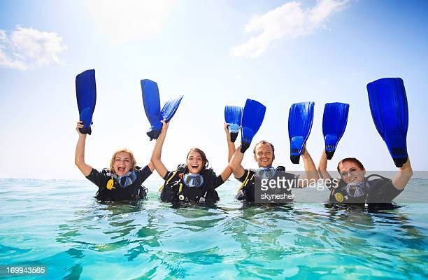 Smiling group of young divers holding flippers.