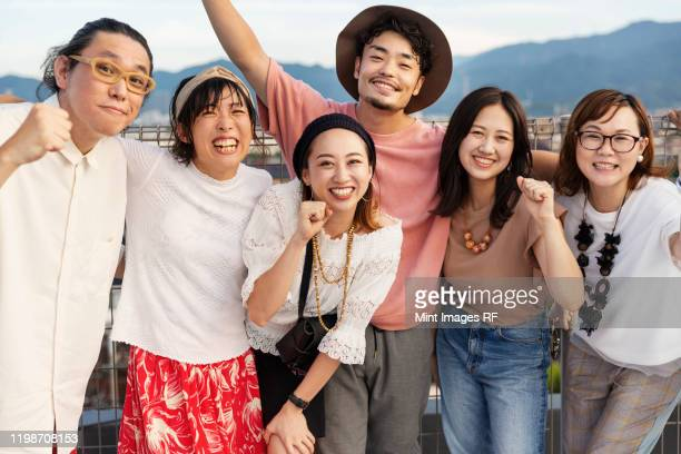 smiling group of young japanese men and women standing on a rooftop in an urban setting. - ヤングアダルト ストックフォトと画像