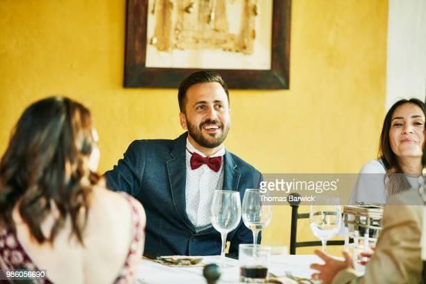 Smiling guests enjoying outdoor wedding reception dinner