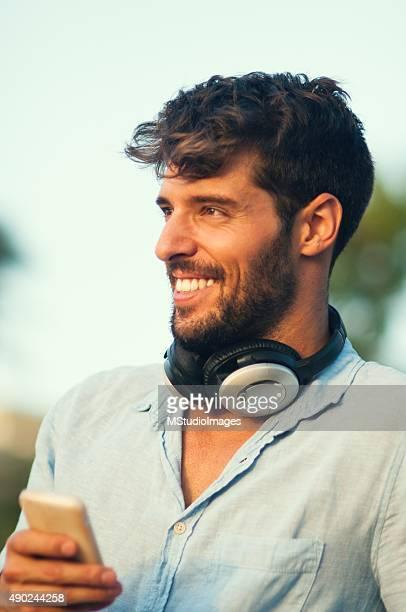 Homem sorridente usando seu smartphone