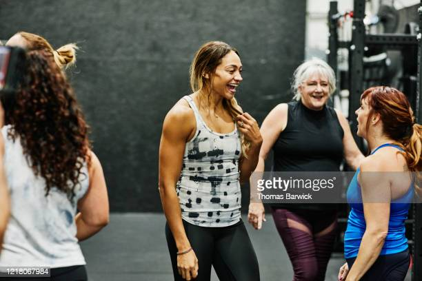 smiling gym owner in discussion with clients during class in gym - instructor stock pictures, royalty-free photos & images