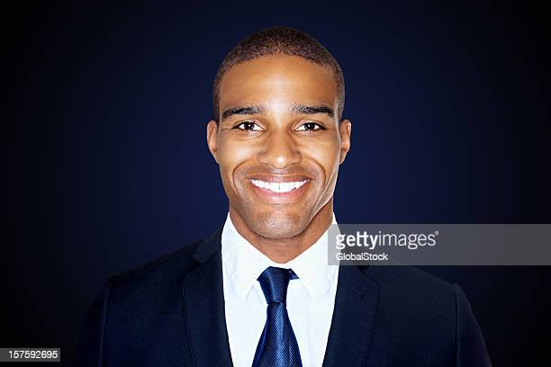Smiling handsome business man isolated against black