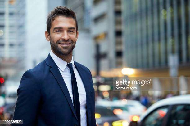 smiling handsome businessman in downtown district - businessman stock pictures, royalty-free photos & images