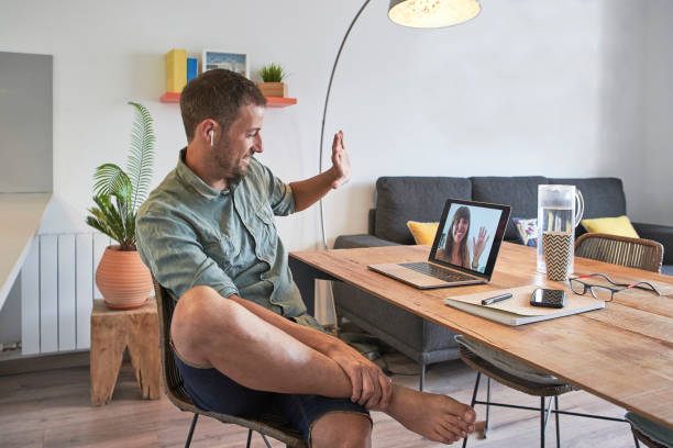 Smiling handsome businessman waving at female colleague through video call on laptop while working from home