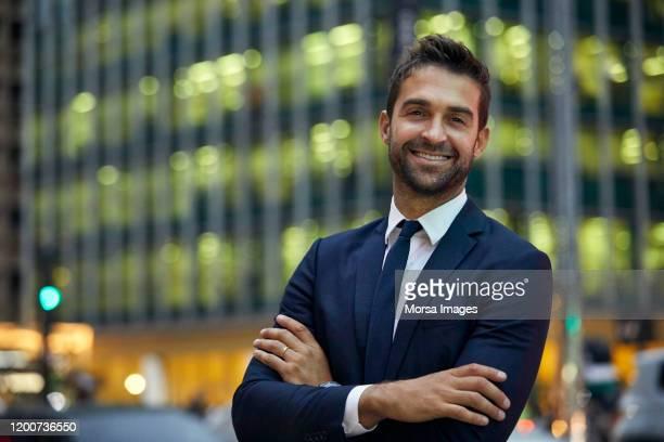 smiling handsome businessman with arms crossed - vestuário de trabalho - fotografias e filmes do acervo