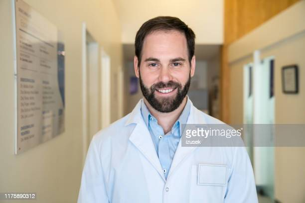 smiling handsome male doctor standing in corridor - izusek stock photos and pictures