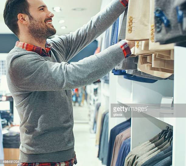 Smiling handsome man buying clothes.