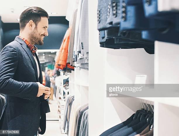 Lächelnd gut aussehender Mann für Kleidung kaufen.