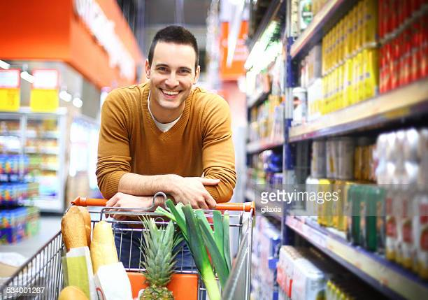 Smiling handsome man in supermarket.