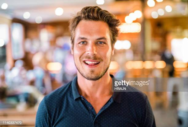 smiling handsome man standing at restaurant - gray eyes stock pictures, royalty-free photos & images