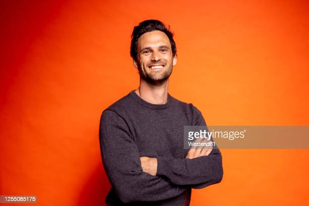 smiling handsome man standing with arms crossed against orange background - coloured background stock pictures, royalty-free photos & images