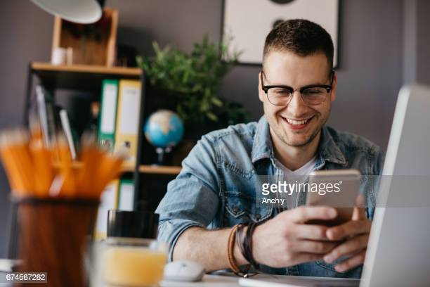 Smiling handsome man using a smart phone
