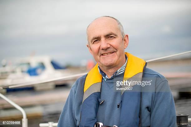 Smiling handsome senior man sailing