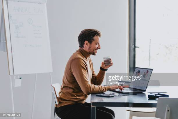 smiling handsome young businessman reading financial reports on his laptop computer in his office - beige stock pictures, royalty-free photos & images