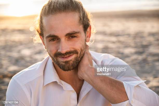 smiling handsome young man relaxing at beach during sunset - escaping stock pictures, royalty-free photos & images