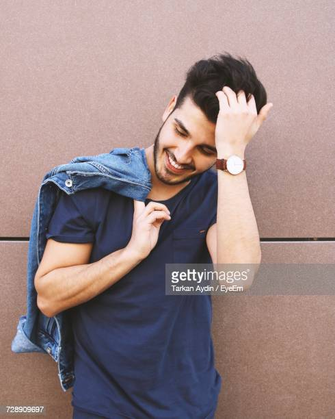 Smiling Handsome Young Man With Hand In Hair Standing Against Wall