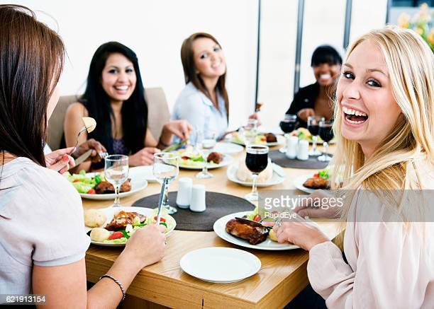 Smiling happily, girlfriends get together to enjoy a friendly meal