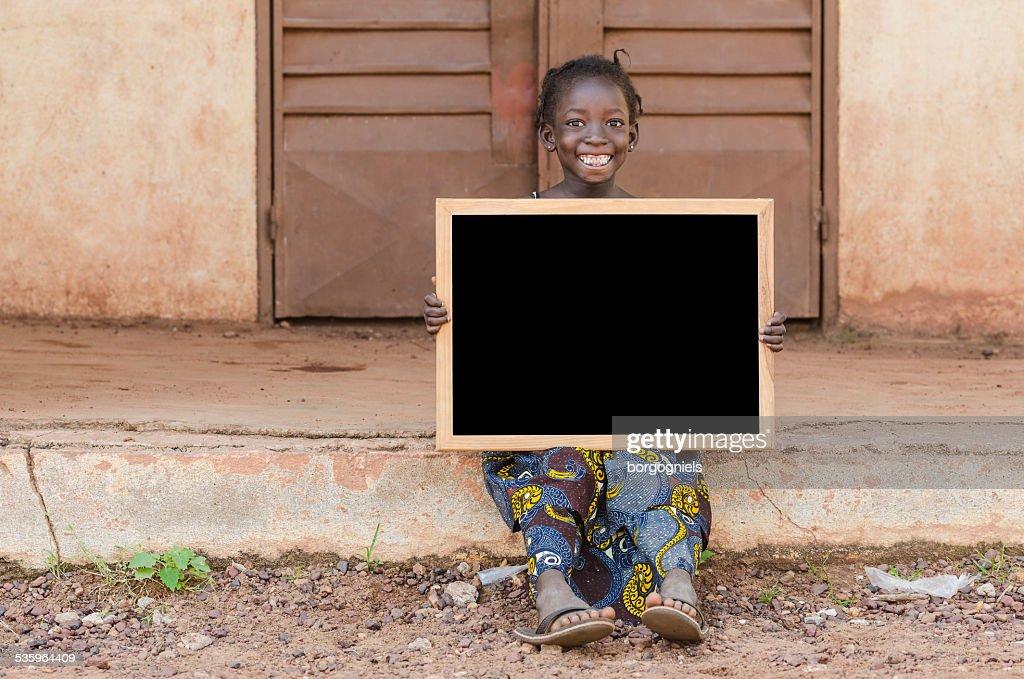 Smiling Happy African Schoolgirl Holding Blackboard Sitting in School : Stock Photo