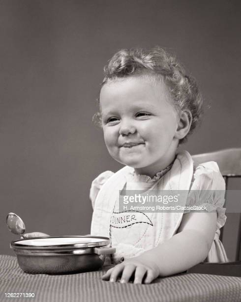 Smiling Happy Baby Girl Curly Hair Wearing Bib Eating With Spoon