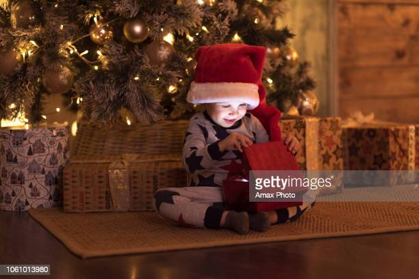 smiling happy cute child in santa red hat holding christmas gift in hand near a christmas tree - santa face stock pictures, royalty-free photos & images