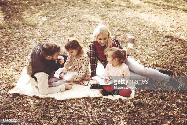 Smiling happy parents with daughter in park and writing together.