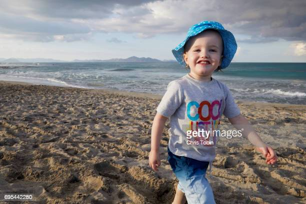 Smiling happy toddler walking on the beach
