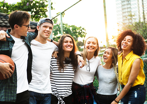 Smiling happy young adult friends arms around shoulder outdoors friendship and connection concept 919536292