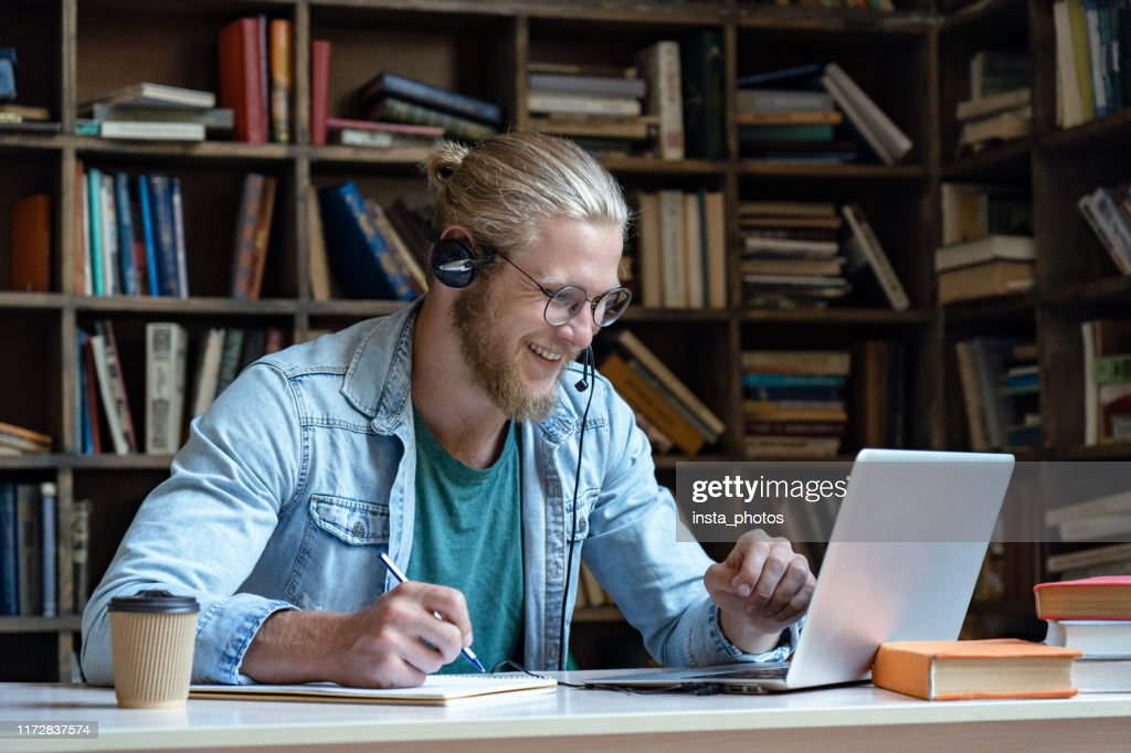 Smiling happy young man wear wireless headset look at laptop screen make notes study e learning in library watch webinar training online course video call, distance education, skype teaching concept : Stock Photo