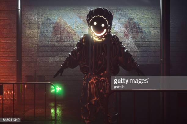 smiling hazmat suit man in the streets at night - dark clothes stock photos and pictures