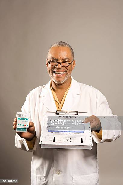 Smiling healthcare worker holding drug test