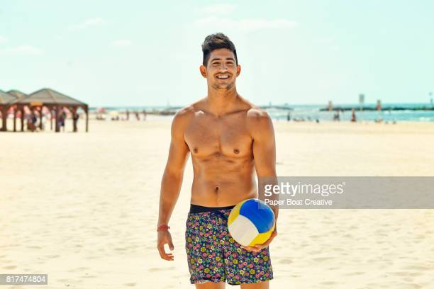 Smiling healthy young man standing playing volleyball on the beach in the summer sun