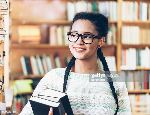 Smiling high school student holding books at library
