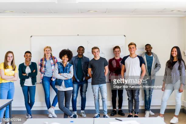 smiling high school students standing in classroom - high school student stock pictures, royalty-free photos & images