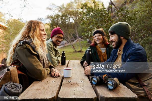 smiling hikers resting and talking together at a picnic bench - wilderness stock pictures, royalty-free photos & images