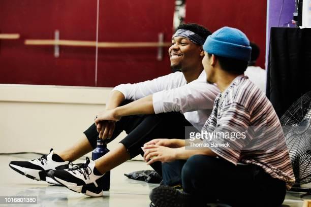 Smiling hip hop dancers relaxing during break in practice in dance studio